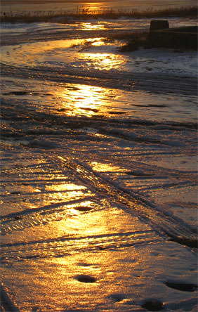 icy tire tracks at sunset